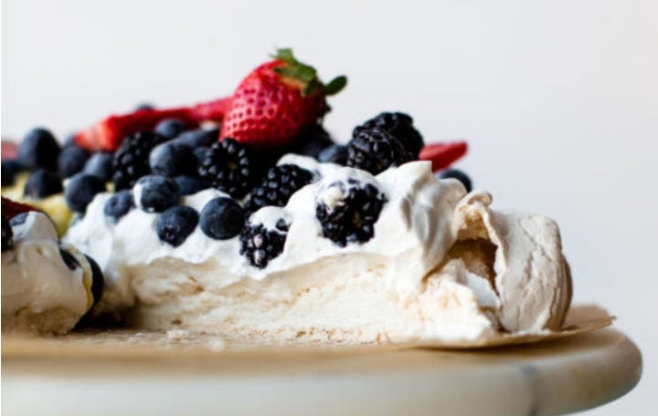 Pavlova cake, topped with whipped cream and fresh berries.