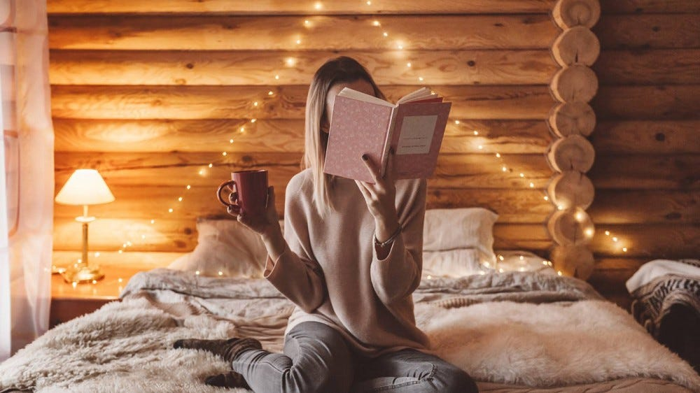 A woman sitting on a bed, holding a mug, and reading a book.