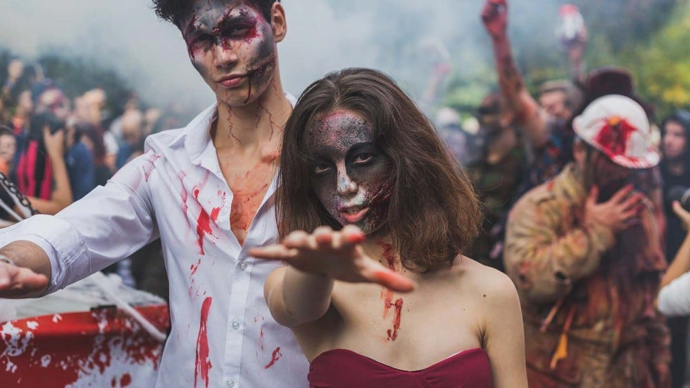 A man and woman in zombie costumes, covered in fake blood.