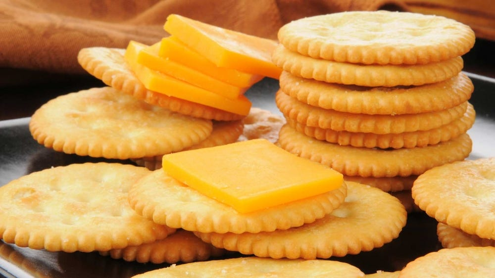 Crackers and cheese piles up on a plate.
