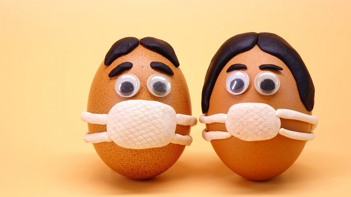 Two eggs with faces painted on them wearing surgical masks.