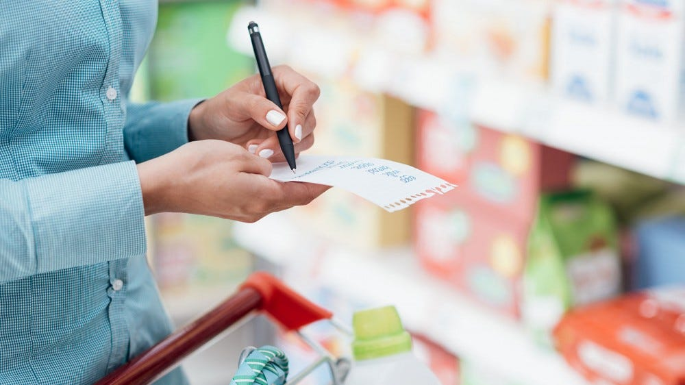 A woman checking items off her list at the grocery store.