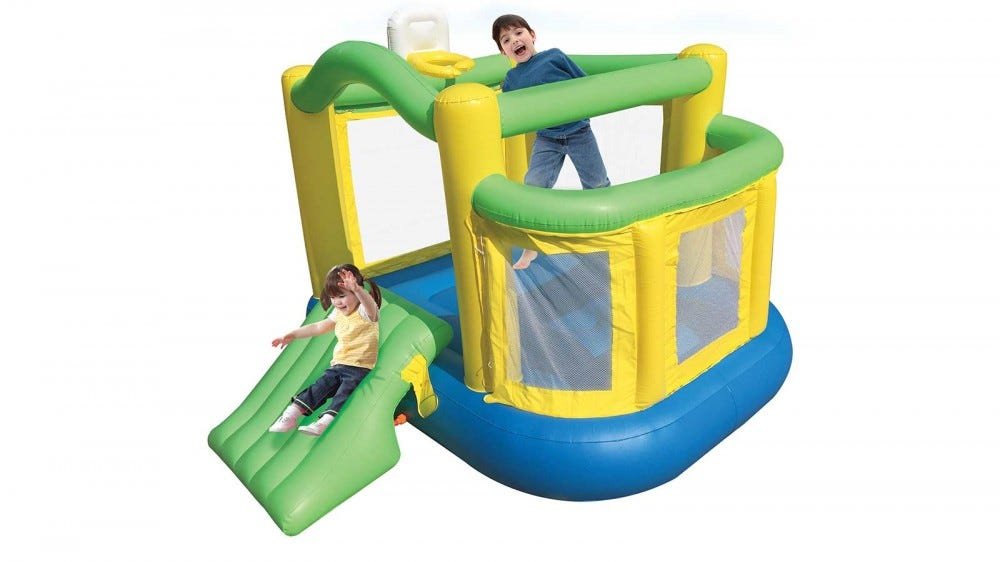 Two kids jumping and sliding on a green, yellow, and blue bounce house.