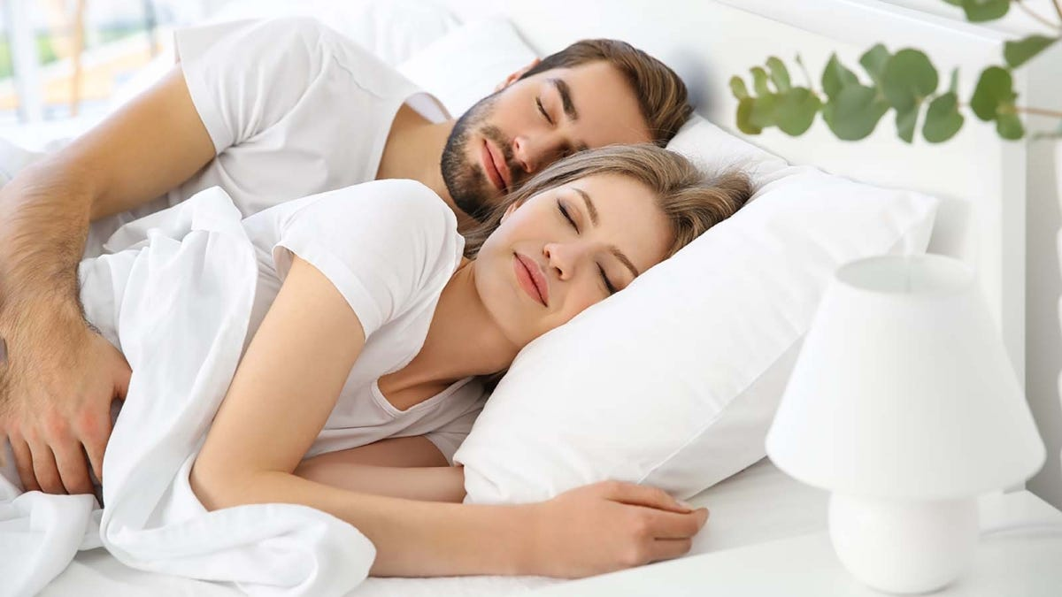 Couple sleeping comfortably in bed together, snuggled up