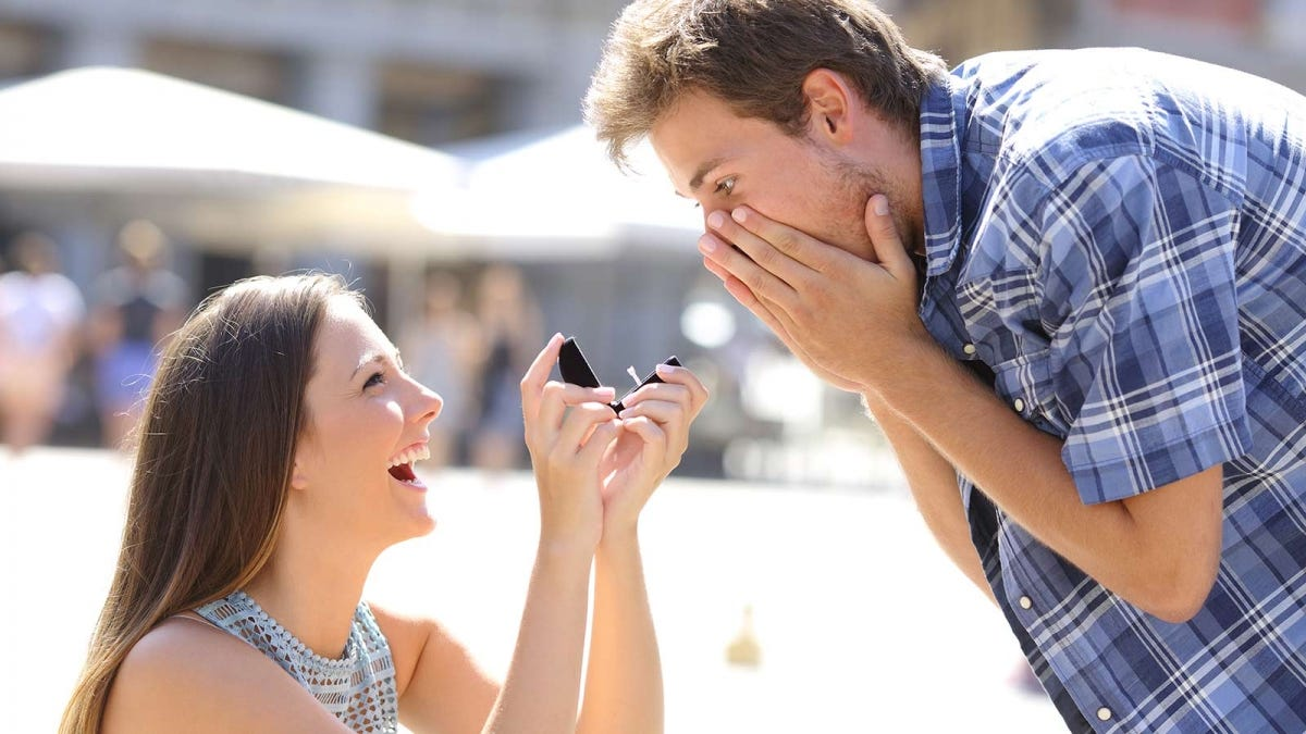 Woman proposing to a man, reversing the traditional gender roles in a marriage proposal.