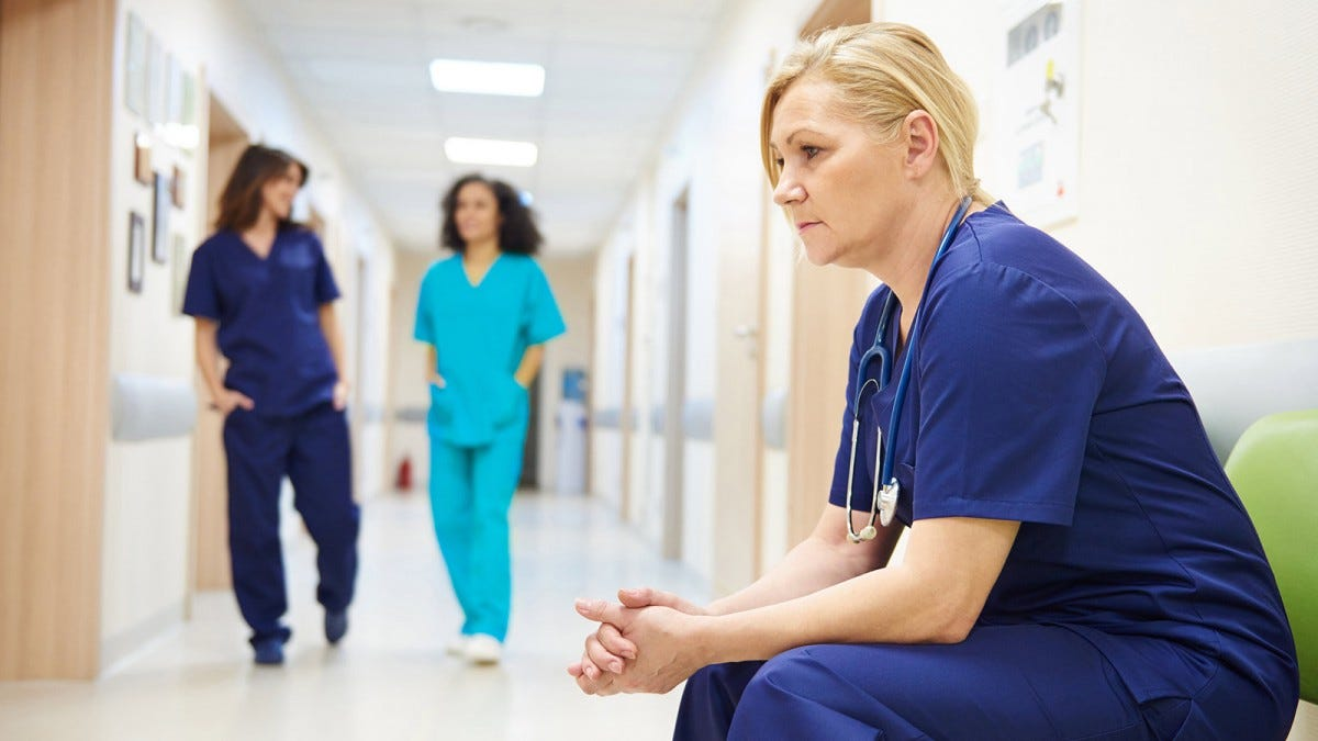 A female health care worker sitting on a bench in a hospital hallway.
