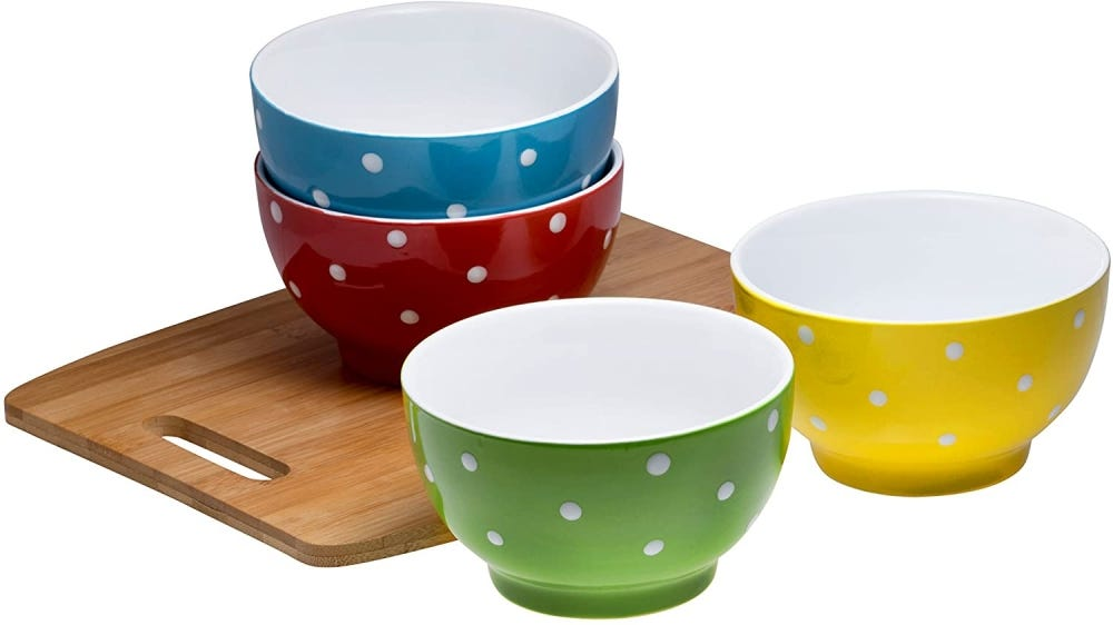 Set of four polka-dot soup bowls on a wooden cutting board.