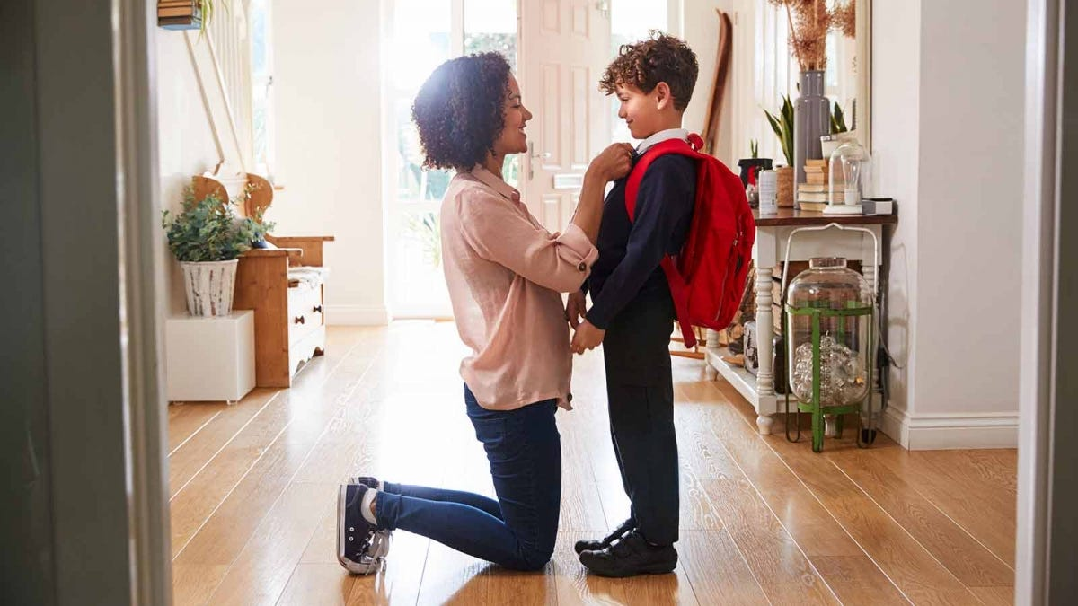 A mom kneeling in front of her son, straightening his tie in a foyer.