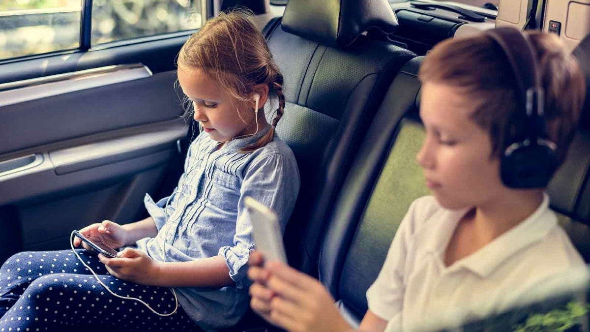 children sitting in the back seat of a car on a road trip, playing with their devices