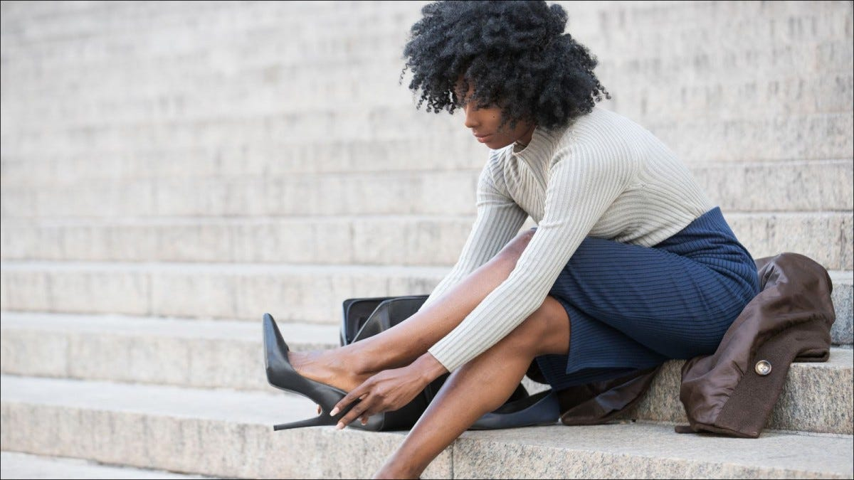 young woman sitting on steps and adjusting high heeled shoes