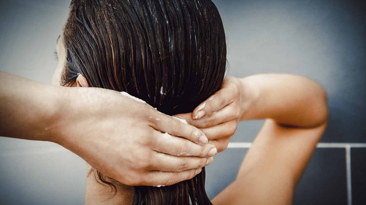 Back of a woman's head as she washes her hair.