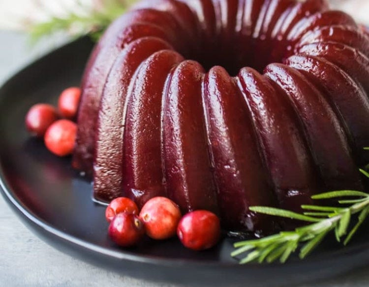 A beautiful molded cranberry sauce that is smooth with fresh rosemary and cranberries to garnish the plate.