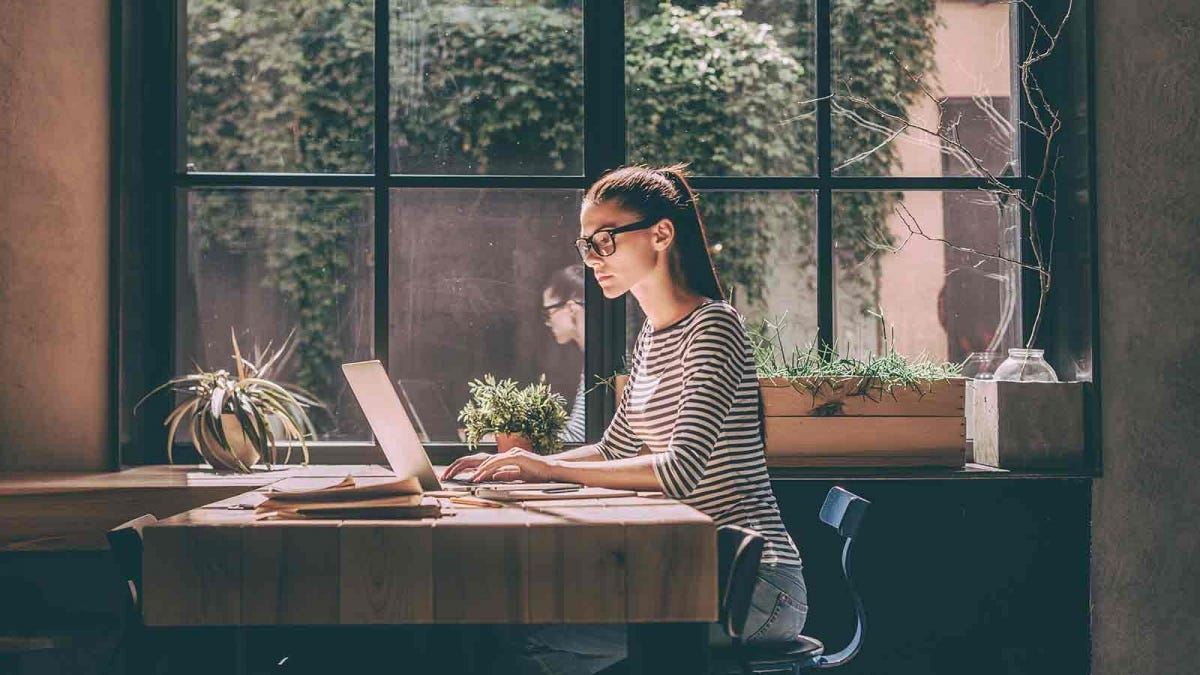 Woman at a desk beside a window working on a laptop.
