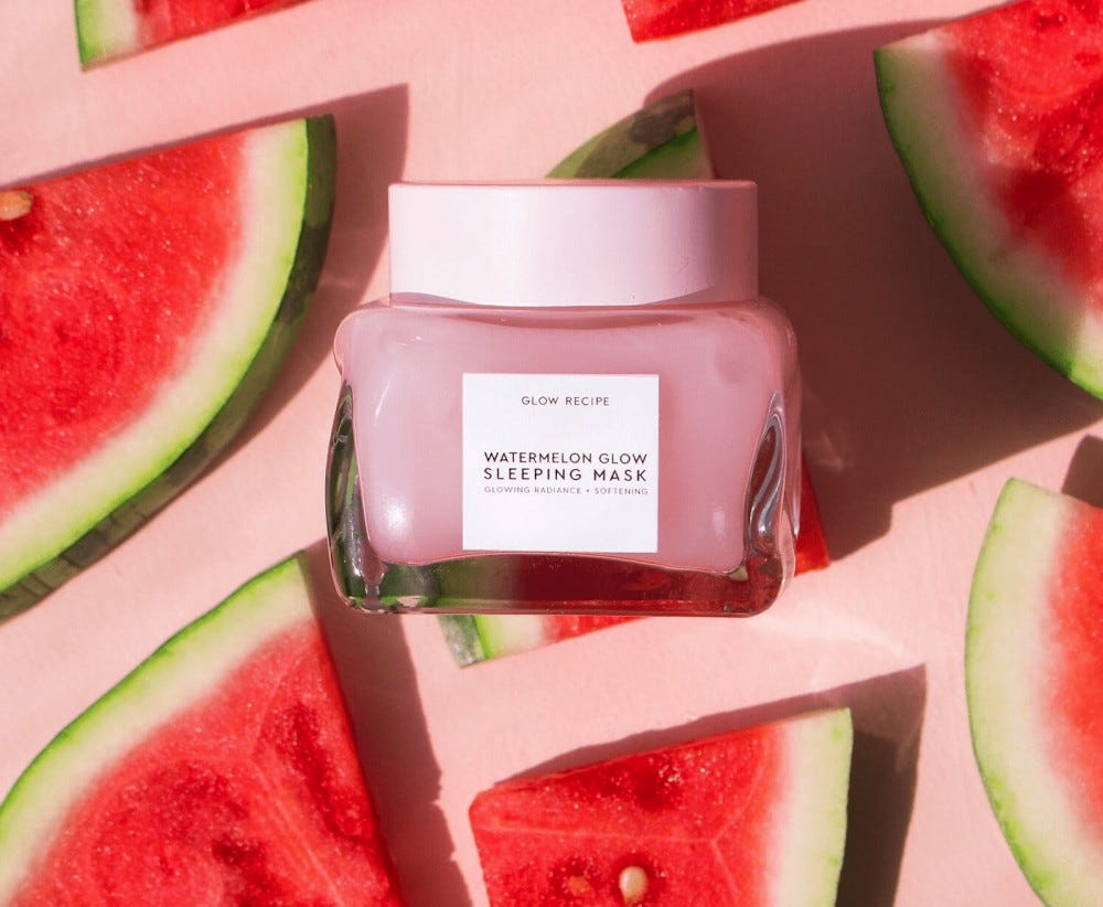 A jar of Watermelon Glow Sleeping Mask surrounded by watermelon slices.