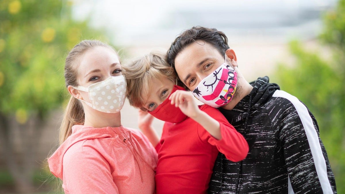 A family wearing cloth masks to help reduce the spread of the coronavirus and protect themselves.