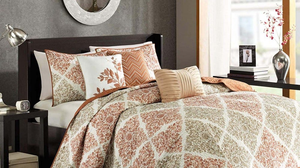 A modern bedroom and bed made up with a fall-themed comforter set that blends modern lines and traditional floral prints.