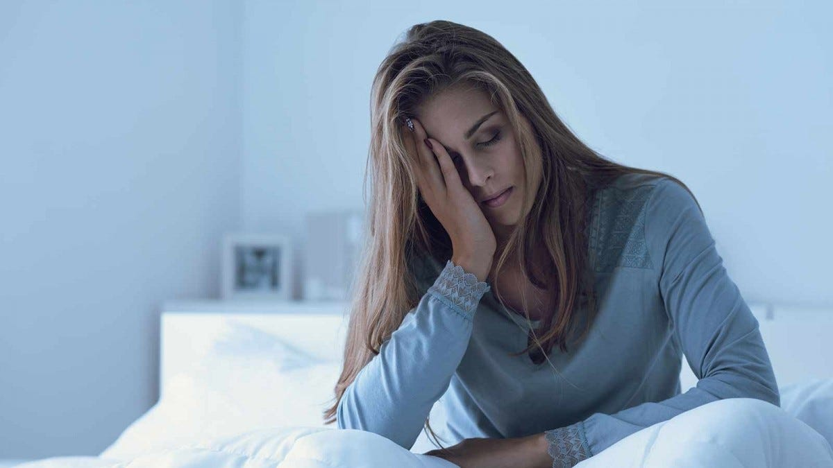 a woman feeling stressed while sitting in bed