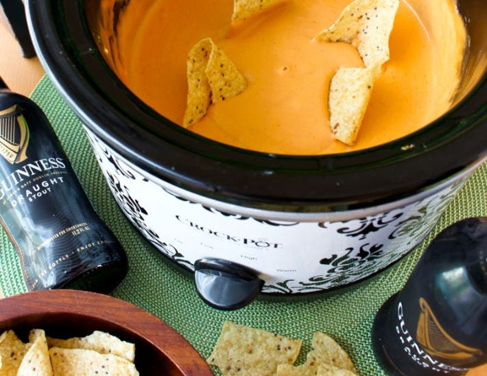 A Crock-Pot filled with Guinness Beer cheese dip, with a few beer bottles and tortilla chips scattered along the side.