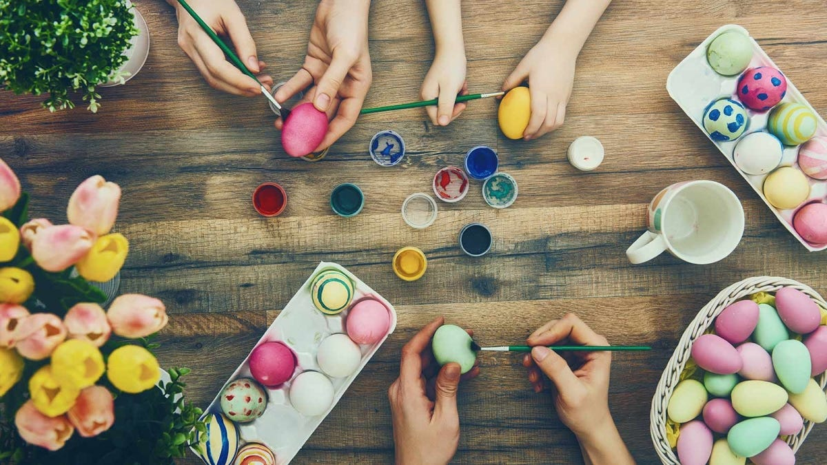 Three sets of hands painting colorful Easter eggs.