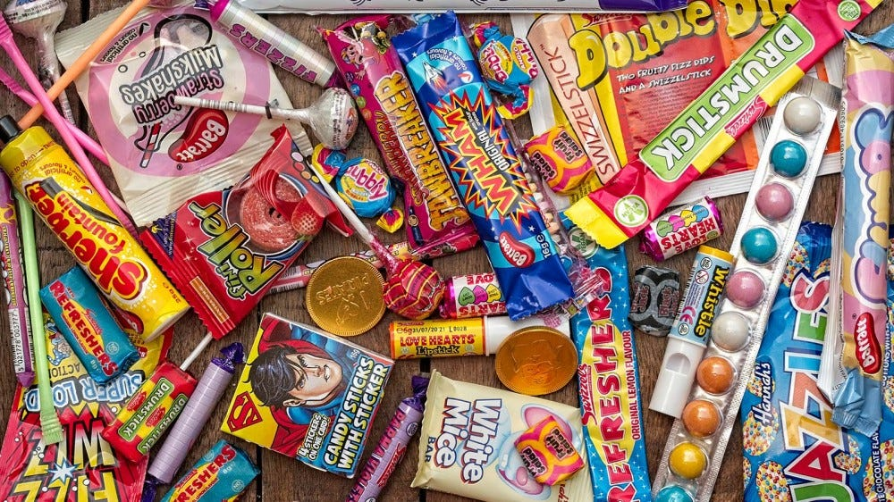 A wooden tray filled with colorful retro candy.