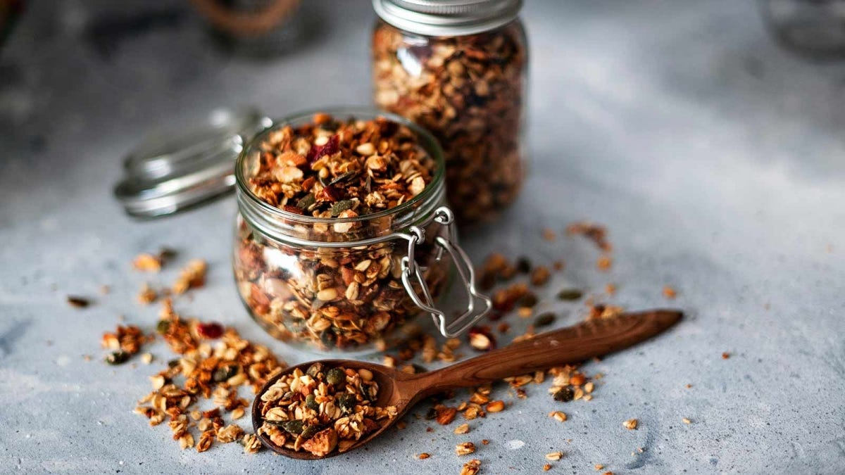 Two jars of homemade granola on a kitchen counter.