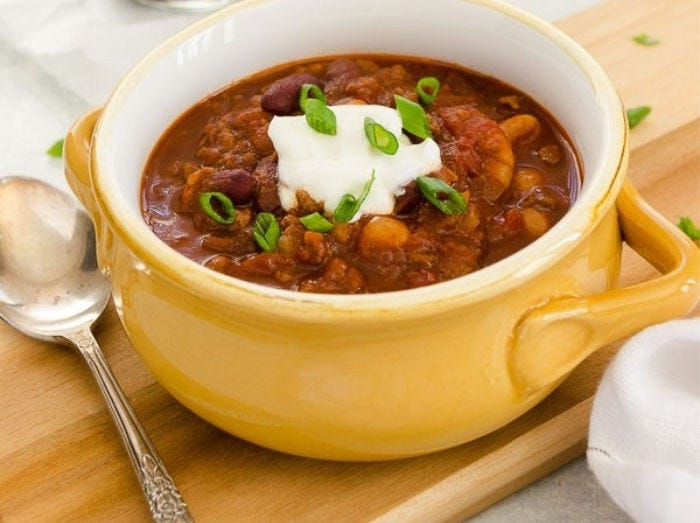 A bowl of beer chili topped with sour cream and green onions, with a soon on the side.