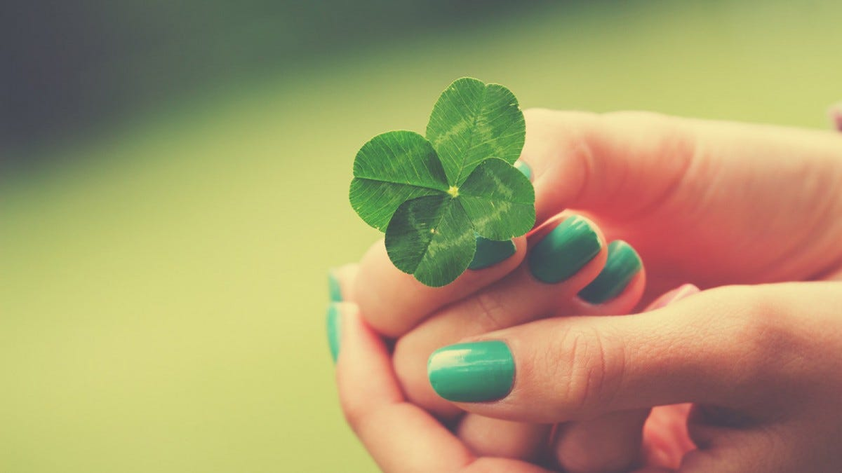 Woman holding a four leaf clover in her hands against a soft-focus background.