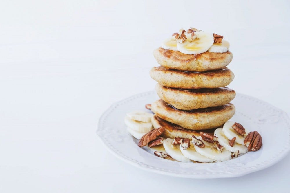 A large stack of grain-free banana pancakes on a plate sprinkled with almonds.