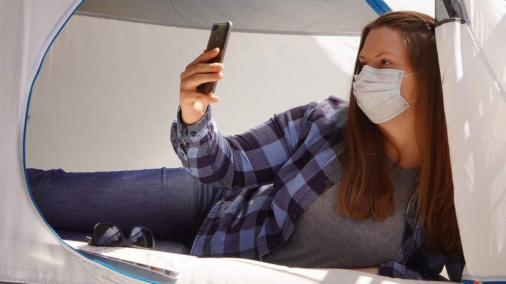 A woman in a tent wearing a mask and taking a selfie.