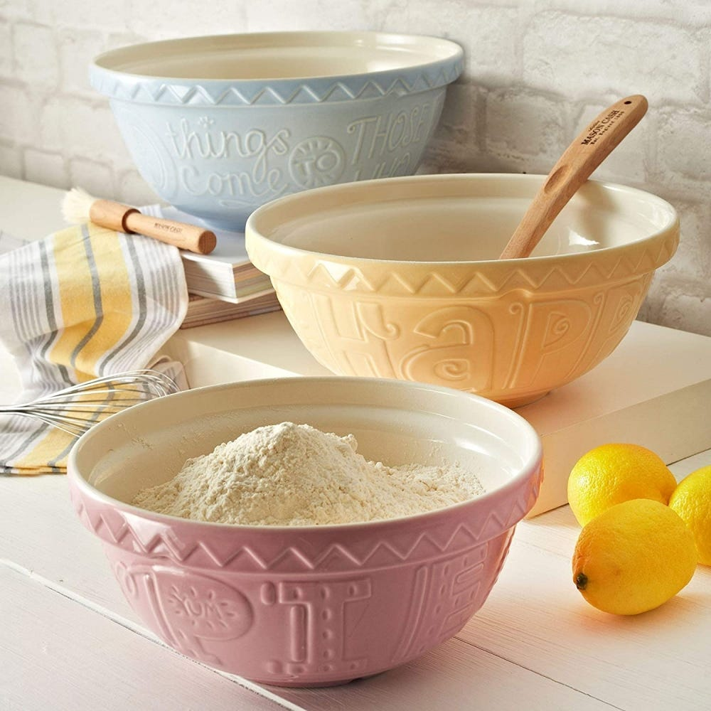 Pink, blue, and beige Mason Cash mixing bowls sitting on a counter surrounded by towels and lemons.