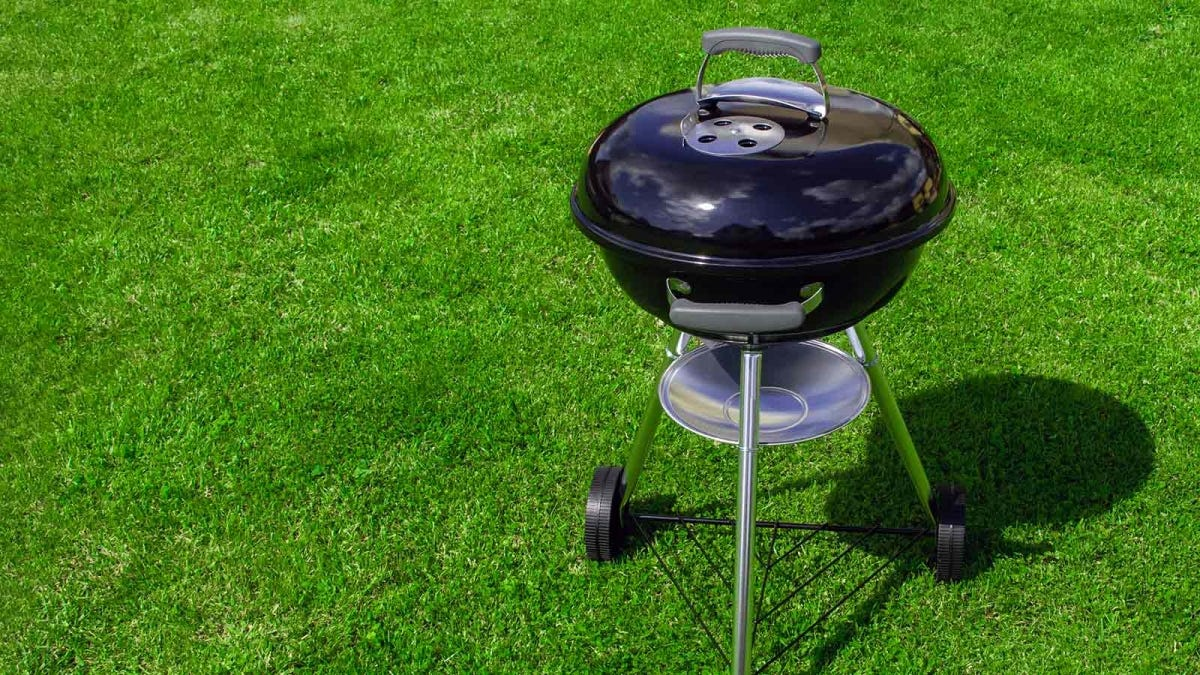 black kettle charcoal grill sitting on a green lawn