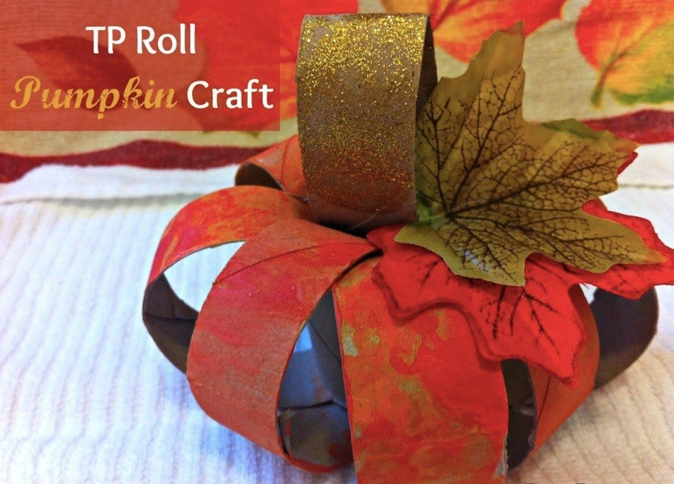 Colorful pumpkin craft made from painted toilet paper rolls and fake leaves