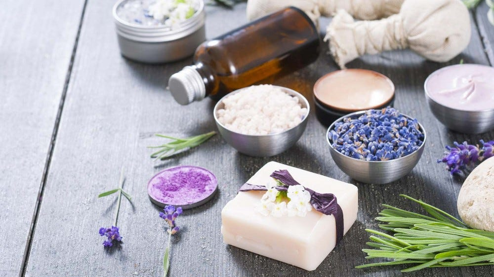 A variety of lavender-based products like soaps, lotions, and more, spread out on a wood table.