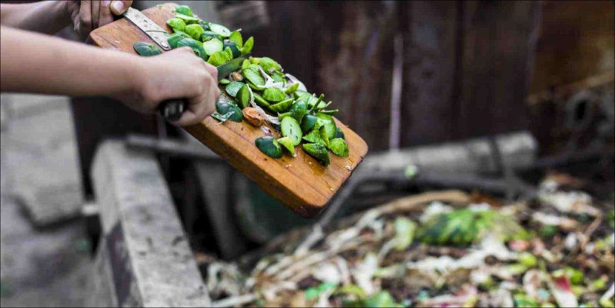 child's hands throwing out kitchen waste from cutting board to garden compost