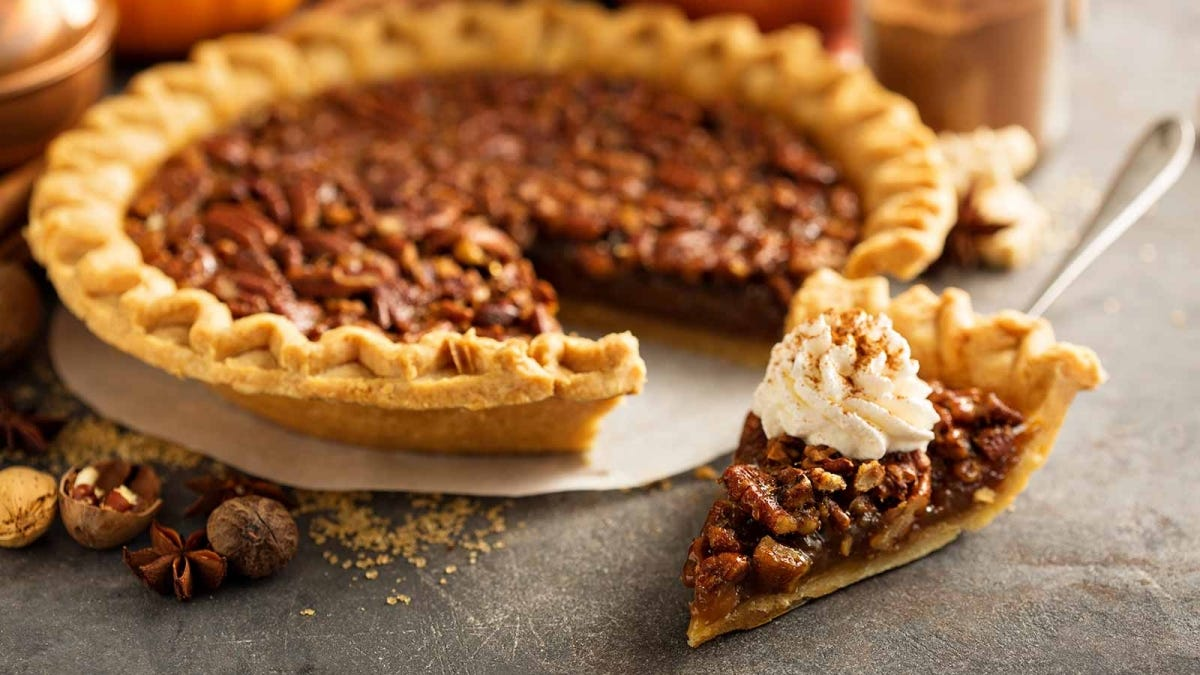 Delicious pecan pie with a slice cut out.
