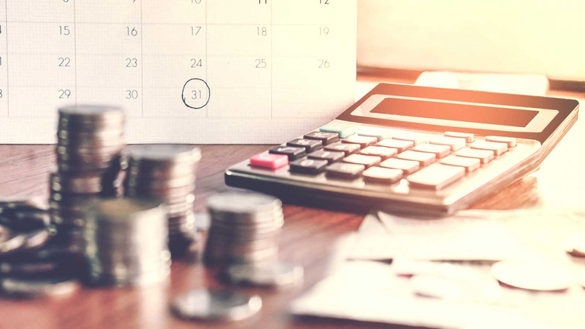 calendar, coins, and a calculator on a table top