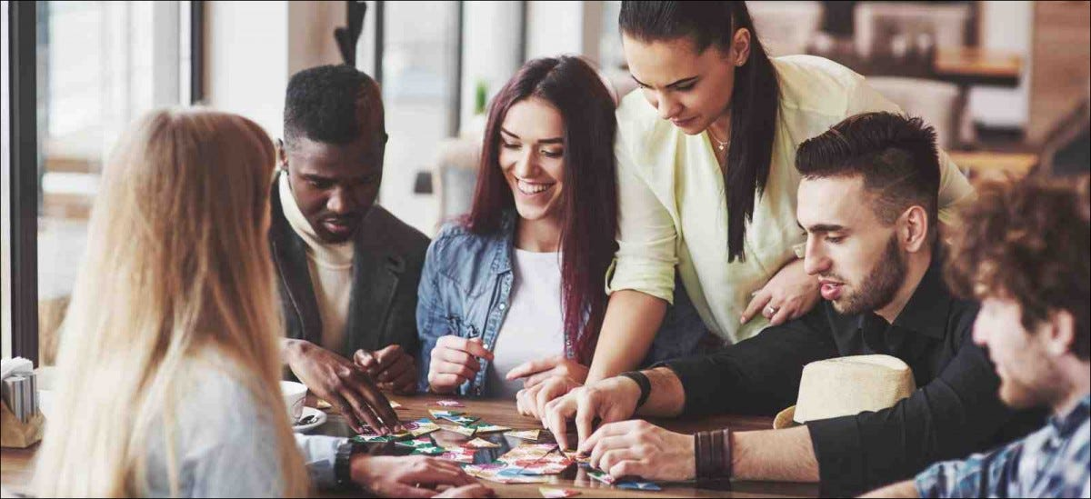 Group of friends sitting at wooden table playing a board game