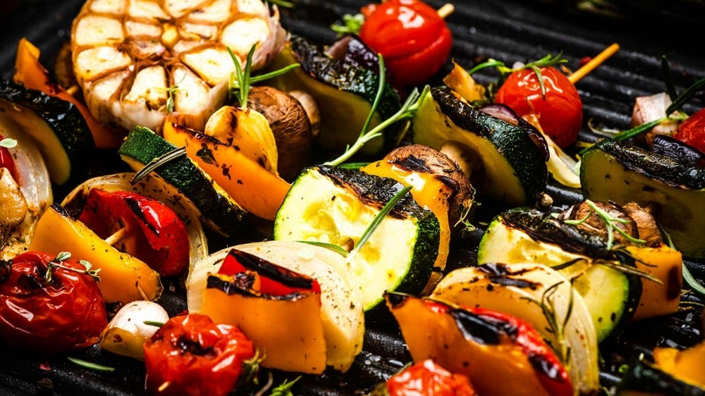 Grilled vegetable skewers resting on a hot grill.