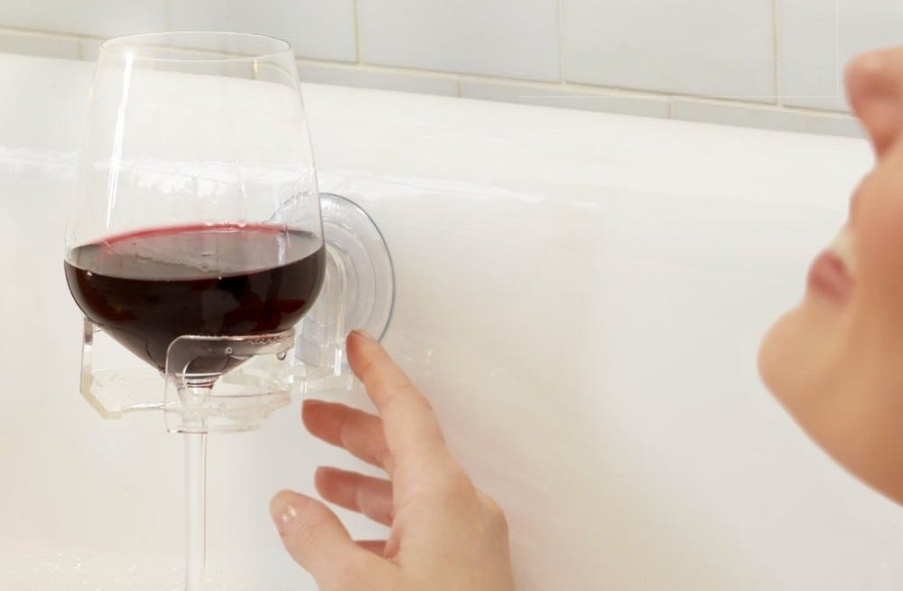 Woman reaching for wine glass in bathtub glass holder.
