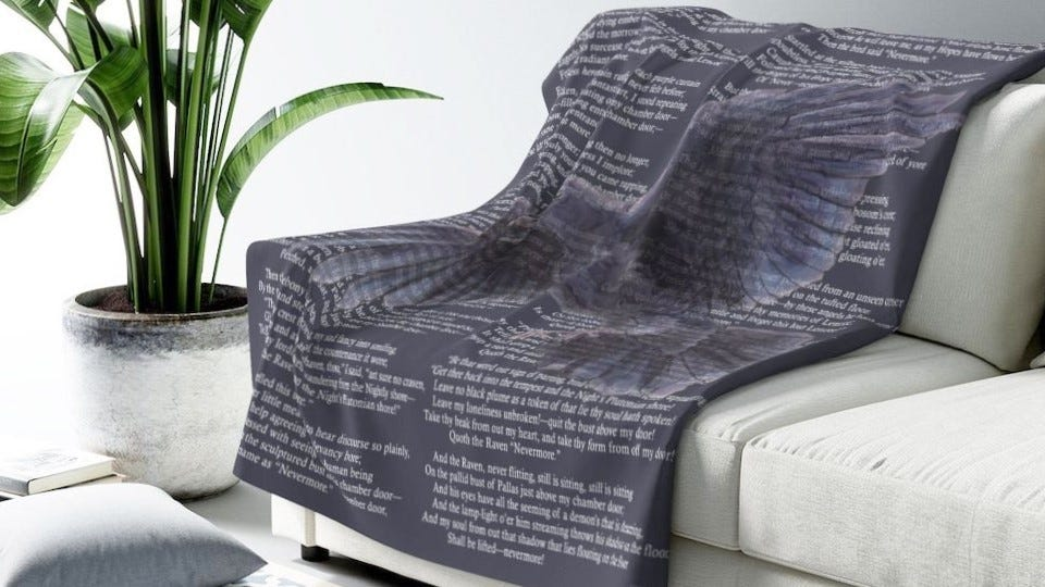 """A cozy fleece blanket featuring quotes from """"The Raven"""" draped over a couch."""