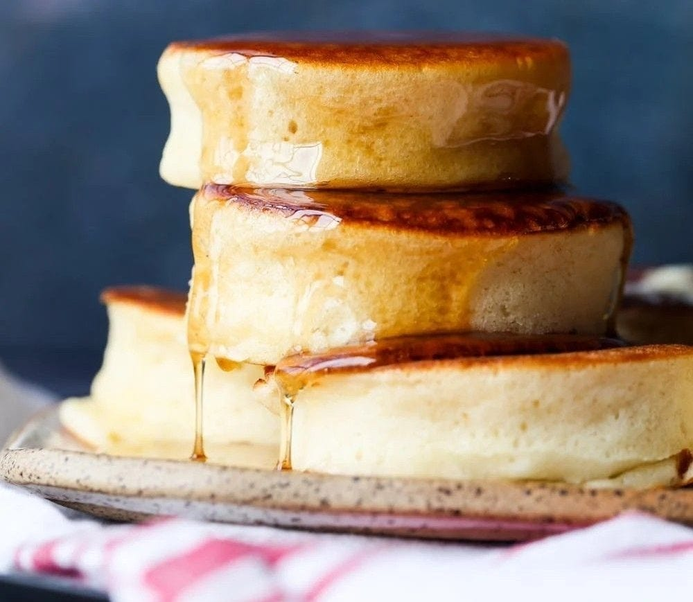 A stack of fluffy Japanese pancakes drizzled with maple syrup.