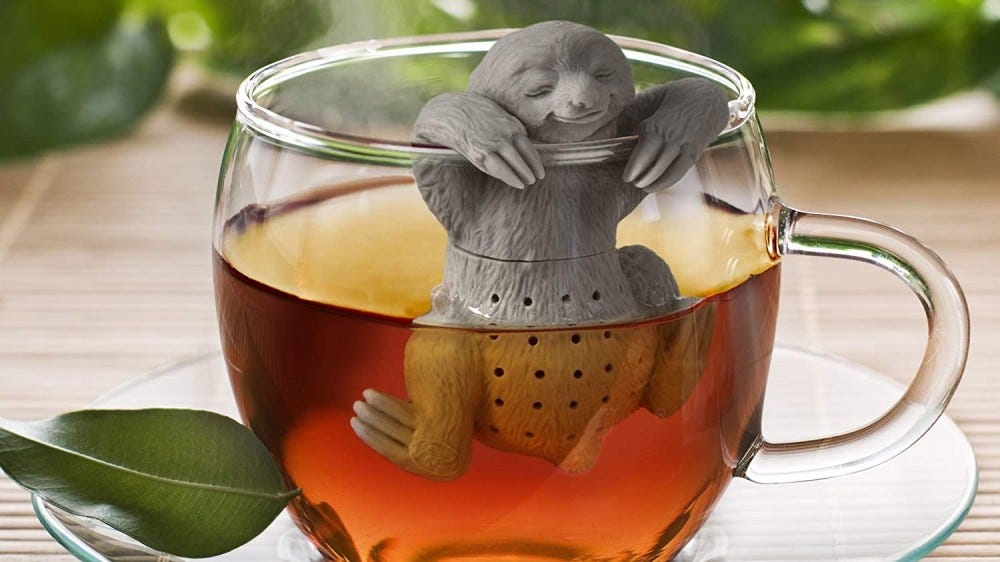 Sloth tea infuser hanging in a cup of tea.