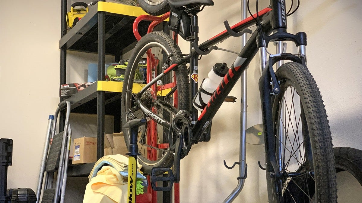 A bicycle hanging on a wall rack next to some storage shelves.