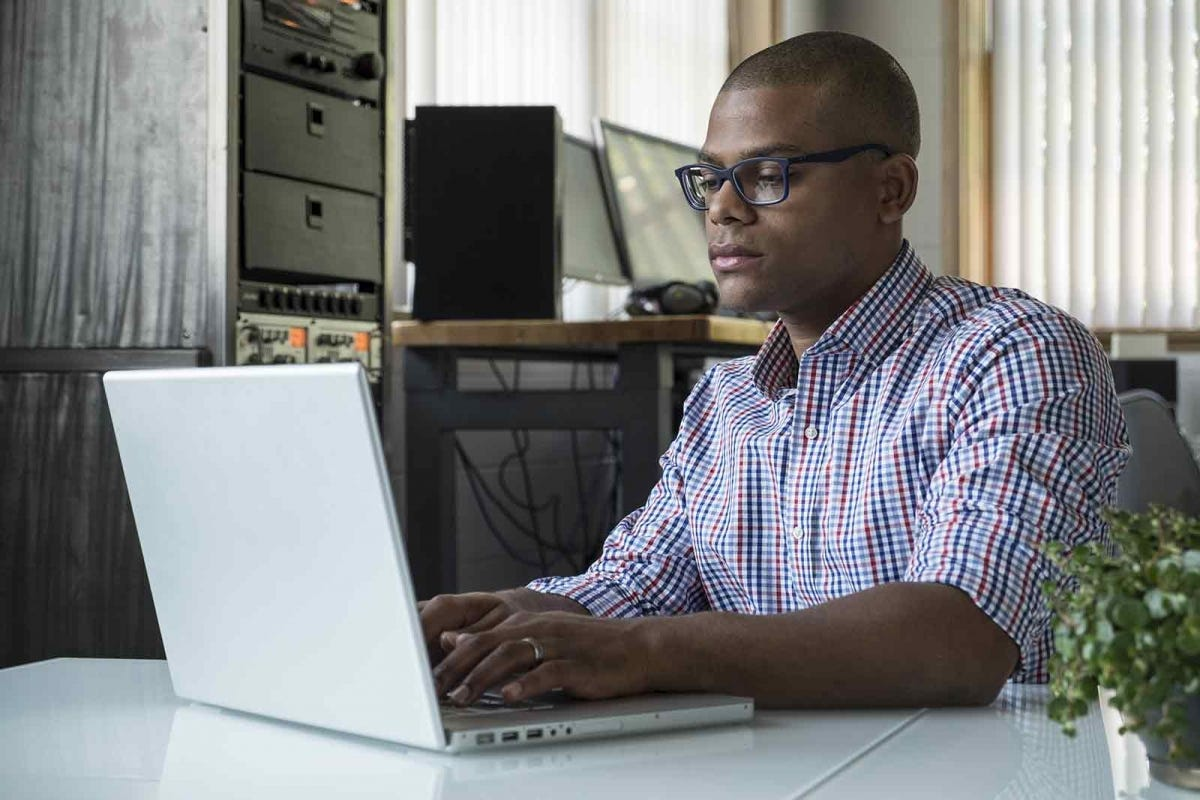 man taking a break from his standing desk to work sitting down with his laptop