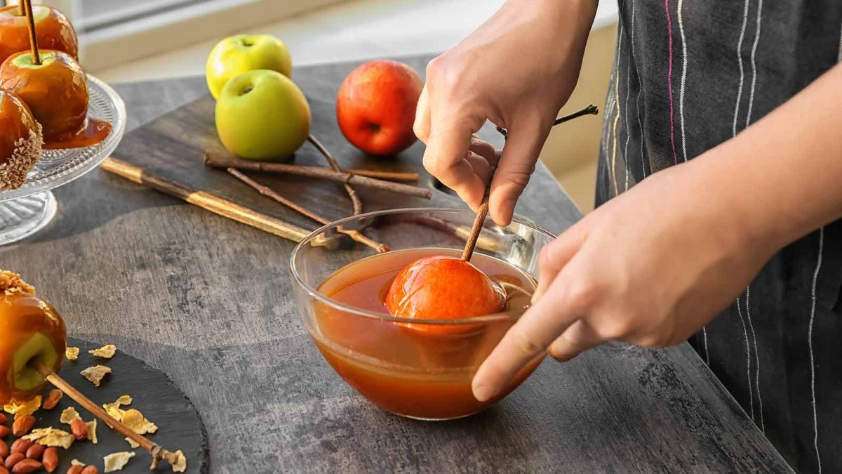 woman dipping an apply in a bowl of melted caramel