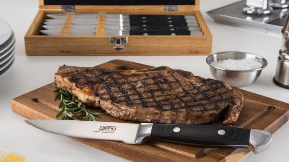 A Viking steak knife on a cutting board next to a ribeye and the full set of Viking knives.