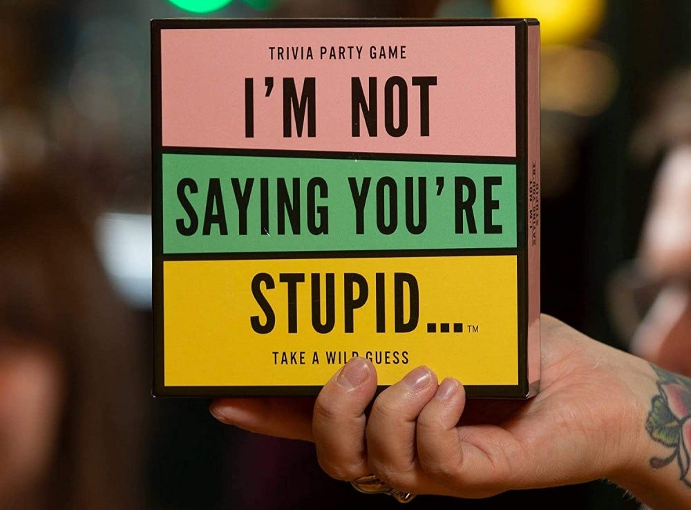 Someone holding the I'm Not Saying You're Stupid trivia game.
