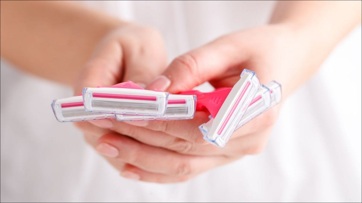 Pink female razors in hands on the white background
