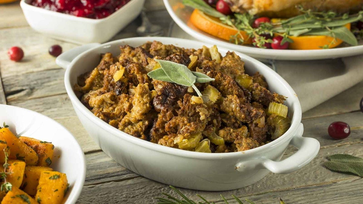 homemade stuffing next to other Thanksgiving dishes on a wooden table