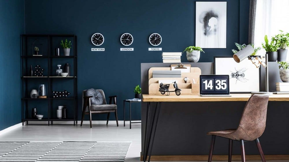 A home office with calm dark blue walls.